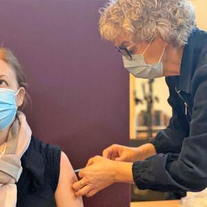 Bilde av helsesykepleier Laila Reitan Sundet som setter vaksine på sykepleier June Vehn Jensvold, som jobber på Buen helse- omsorgssenter. Denne dagen hjalp hun også til med vaksineringen på Melhus bedehus.