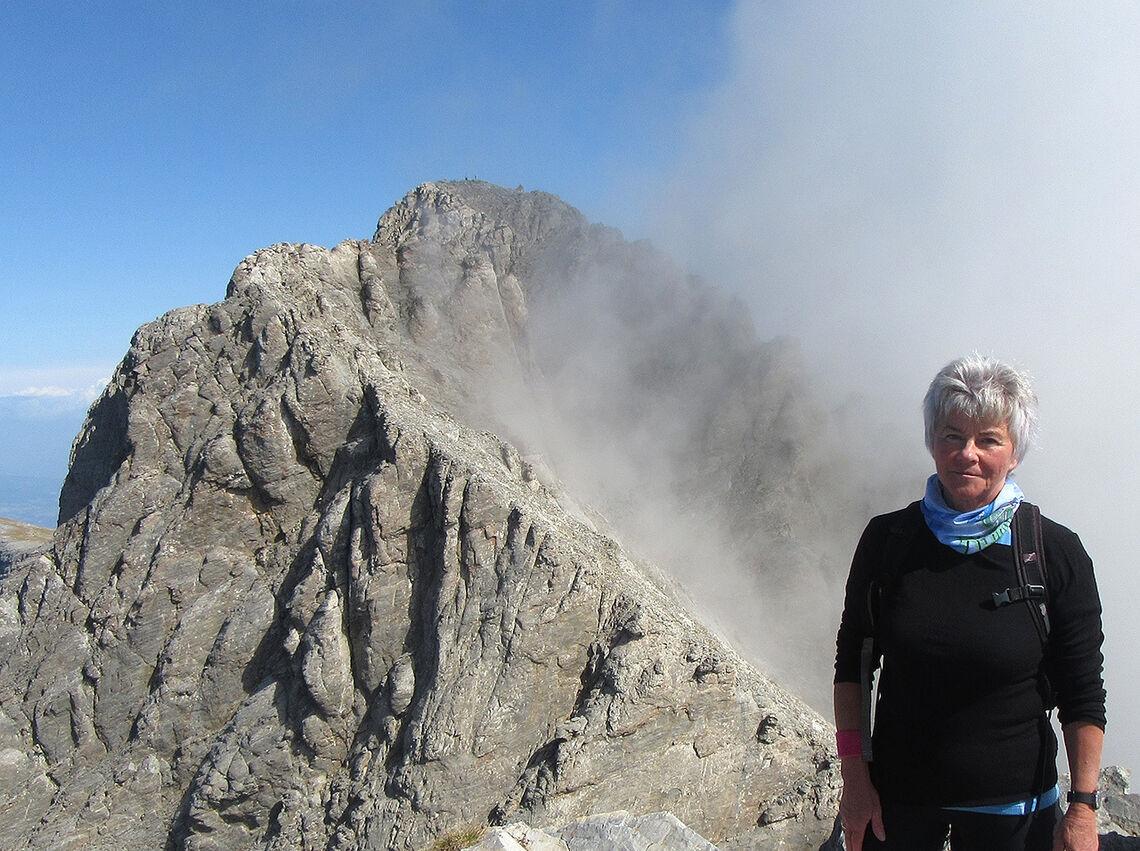 Høyt oppe: Artikkelforfatter Else Husa står på toppen av Skala (2885moh.) med den høyeste toppen Mytikas (2917 moh.) i bakgrunnen. Avgrunnen mellom de to toppene kommer ikke frem på bildet. (Foto: privat)