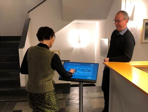 Rådmann Ellen Njøs Lillesvangstu prøver ut den nye besøksregistreringsterminalen medan ordføraren ser på.