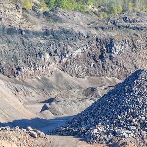 Bilde av et stort grustak med store og små steiner i ulike hauger. Små busker nederst i bildet.