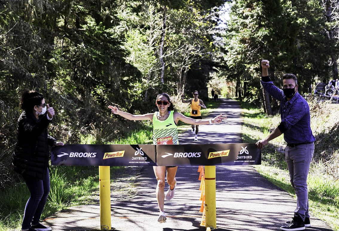 Fartsholder Charlie Lawrence har sluppet henne fram, og Des Linden krysser målstreken som vinner på ny bestetid i verden på 50 km. (Foto: Brooks Running)