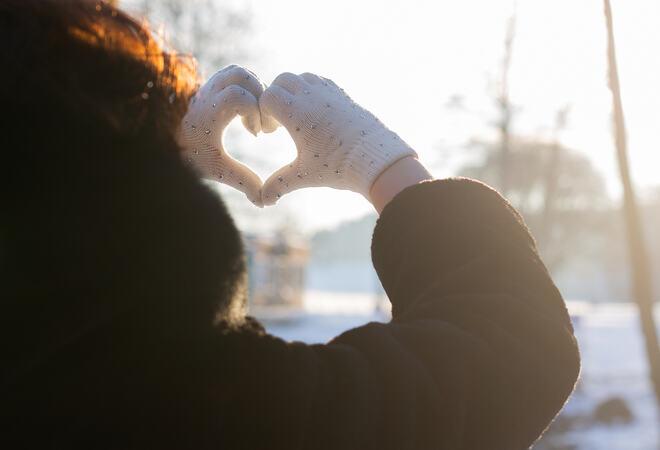 Kvinne med ryggen til som lager hjerte med hendene i vinterlandskap