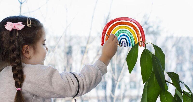 Illustrasjonsbilde av karantenetilværelse - en jente som tegner regnbue på et vindu