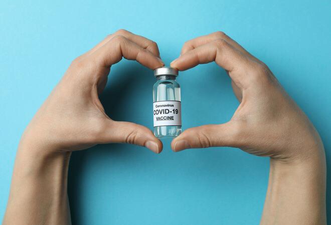 Hender i hjerteform som holder hetteglass med covid-19 vaksine.
