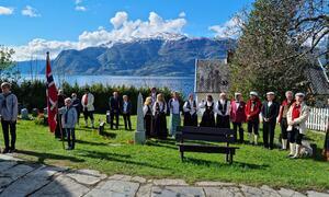 Representantar frå kora på Leikanger syng ved kyrkja