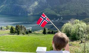 Utsyn frå altan mot båtkonvoi på fjorden