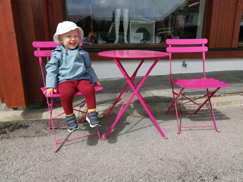 Blid unge ved eit rosa utebord