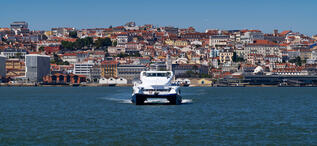 A ferry boat crossing the Tagus River (Rio Tejo) with the city of Lisbon skyline on the background, in Portugal