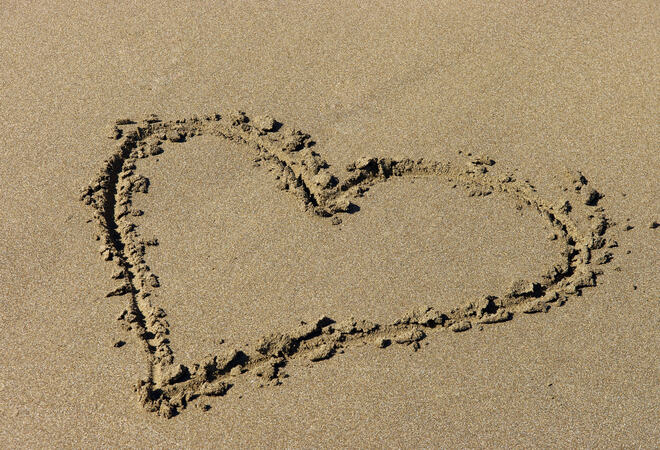 a heart is drawn in the sand on the beach
