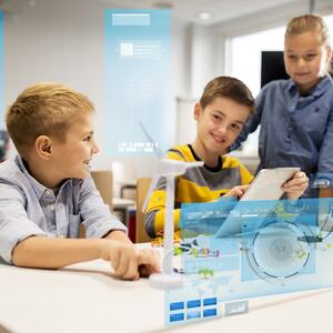 To gutter sitter ved en skolepult, en jente står ved siden av. Den ene gutten holder et nettbrett. I bildet ser man tre grafiske elementer som er blå.