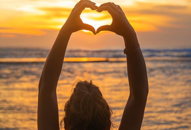 Girl makes heart hands at sunset. Sri Lanka. Selective focus.