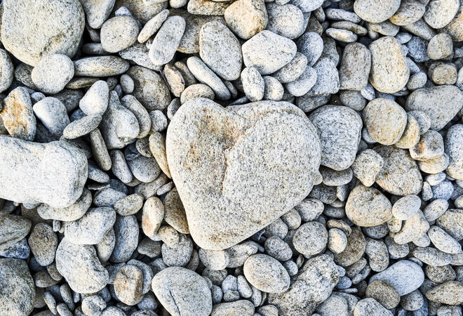 A heart-shaped stone on a pebble beach in France.