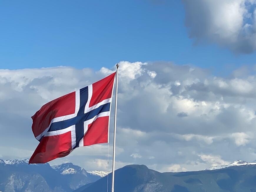 Norsk flagg som vaiar i vinden.
