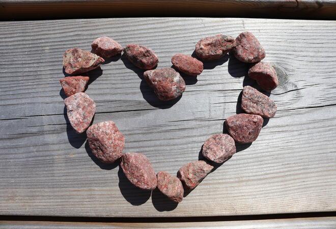Steinhjerte av røde småsteiner på treplatting.