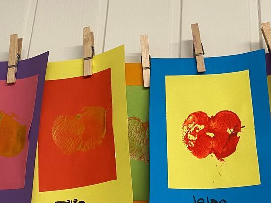 Barnehagekunst. Fargerike ark med trykk av eple som heng på ei snor.