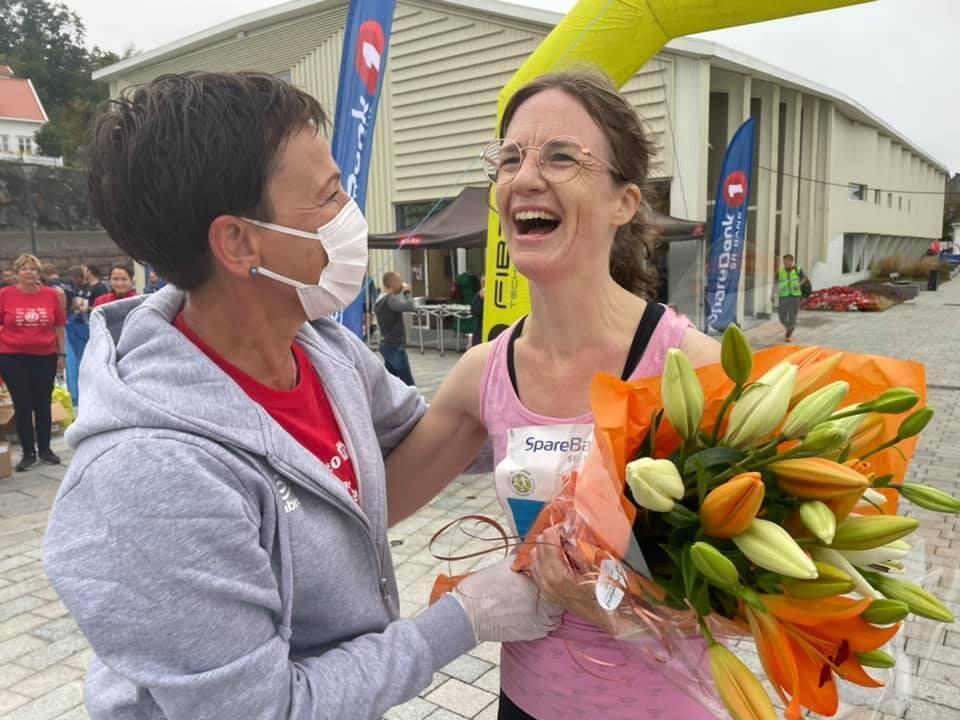 Arrangøren delte ut fire blomsterbuketter til noen de plukket ut i farta, her er det en lykkelig 5 km løper som ble overrasket med blomster av funksjonær Beate Sommer. (Alle foto: Janicke Yttervik )