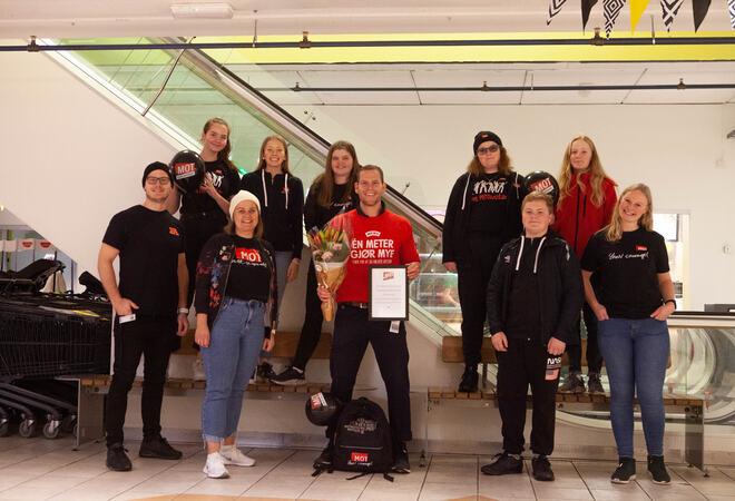 Ei gruppe personar oppstilte mot kameraet med klede med mot-logo. Fjorårets vinnar i midten med blomar og diplom.