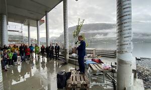 Mann i dress står på ein palle og snakkar i mikrofon. Publikum står og lyttar.