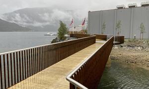 Trebru sett mot grå fabrikkbygning. Norske flagg.