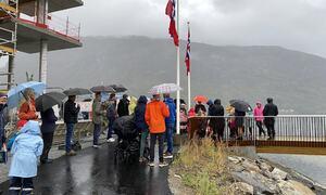 Folk med paraply, norske flagg, enden av brua.