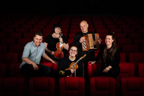 Fem musikarar med instrument som smiler inn i kameraet.