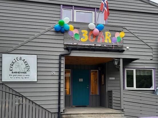 Inngangen til barnehagen, blå dør og grått bygg. Flagg, ballongar og skrifta 30 år over døra.
