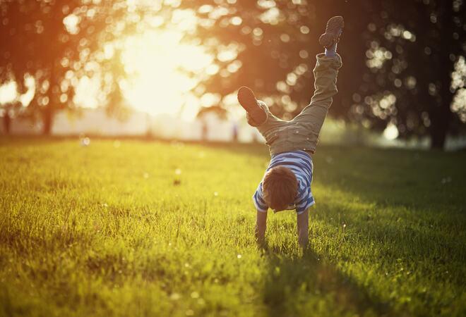 Eit barn som står på hender på grasplen i motlys.